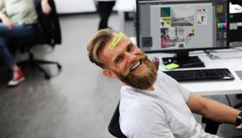 офисный сотрудник улыбается в камеру, на лбу стикер с напоминанием о текущей задаче, чтобы не забыть